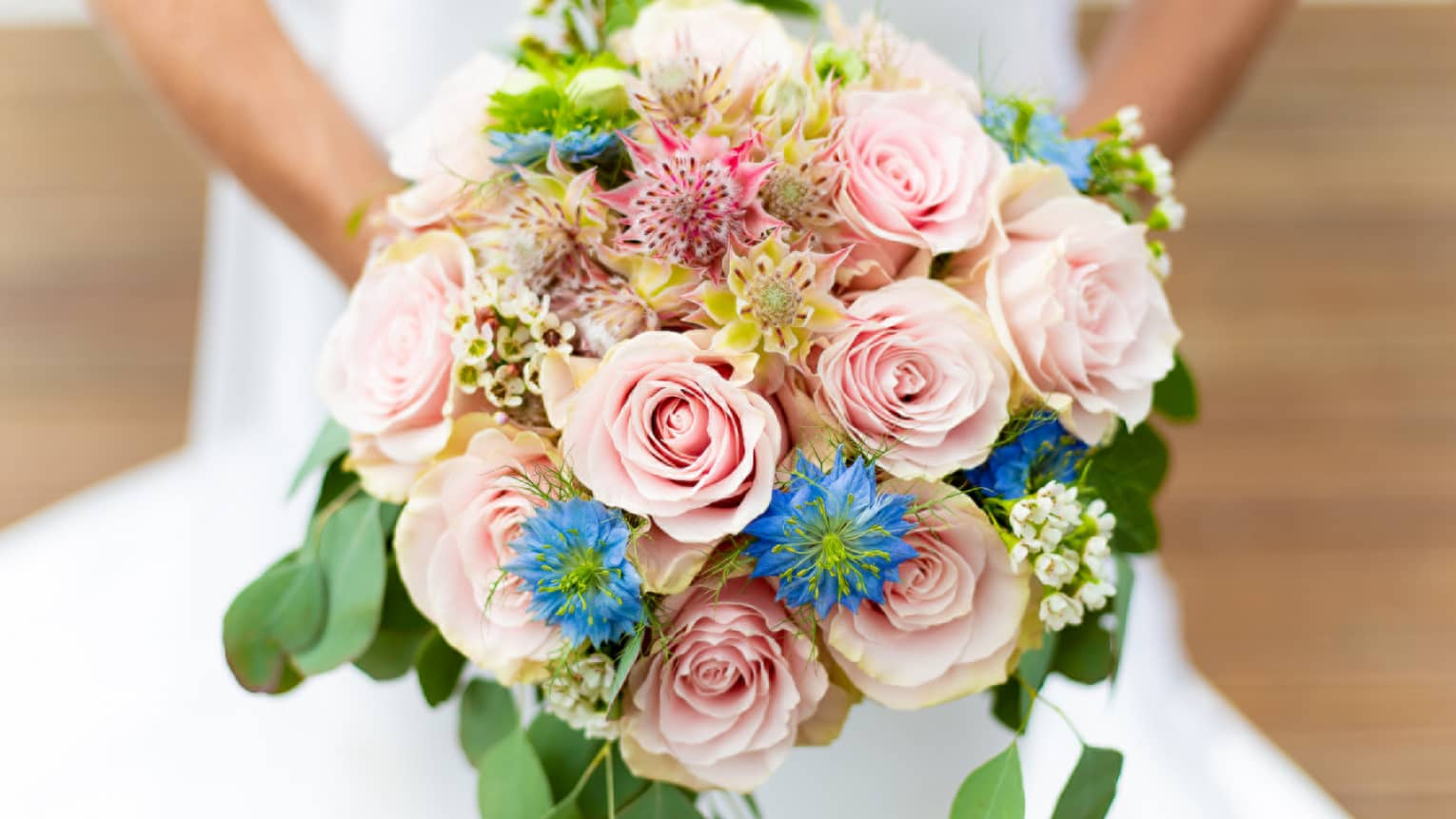 Close-up of bride holding floral wedding bridal bouquet with pink roses, blue flowers