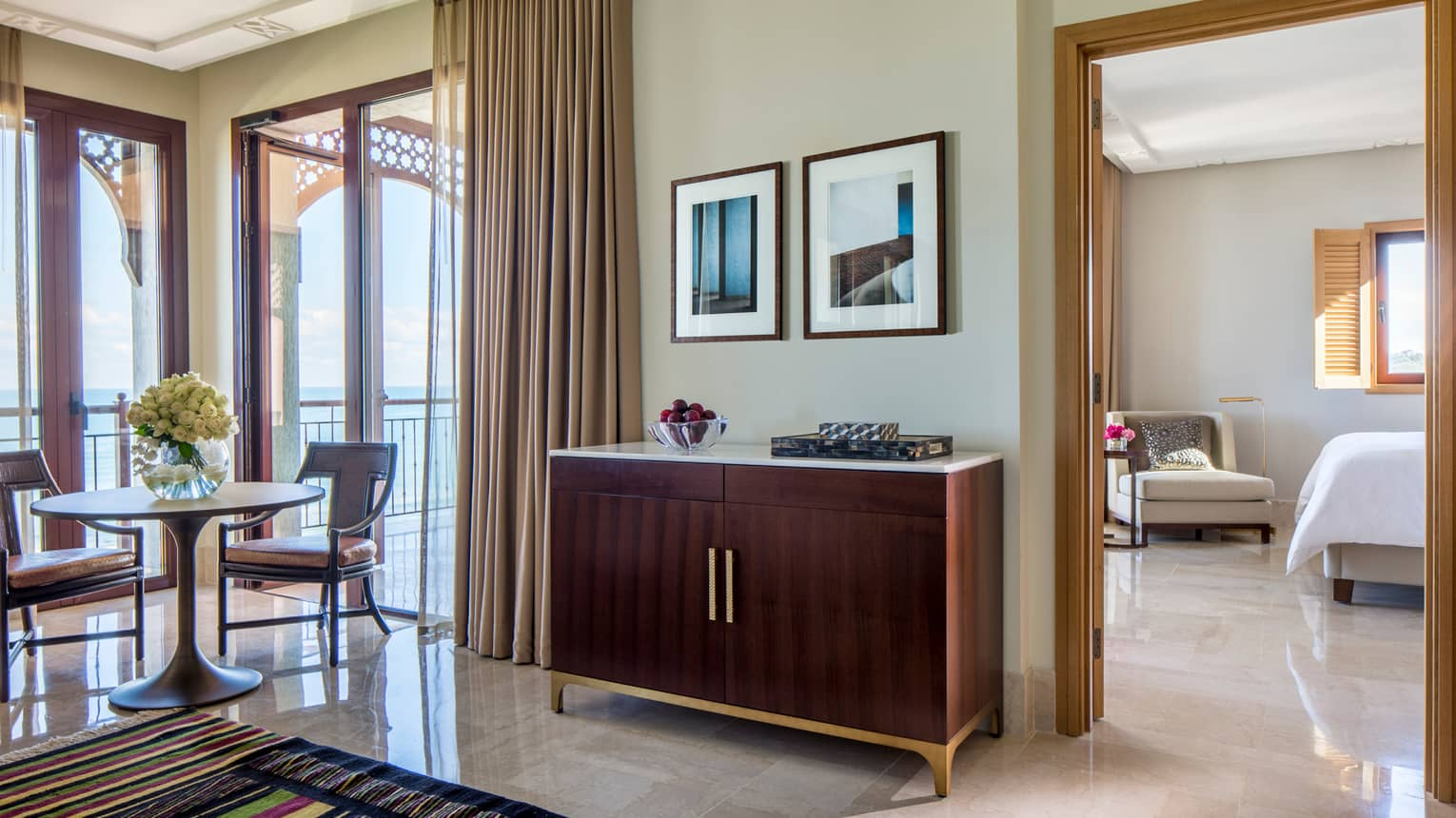 Four Seasons Sea-View Suite wood vanity with bowl of plums, small dining table by sunny window