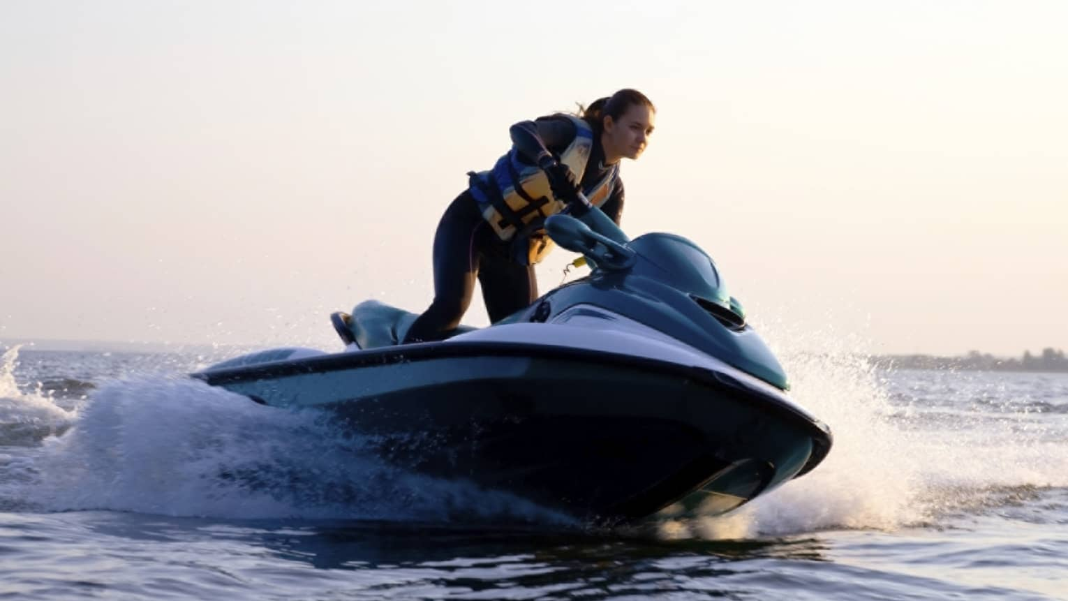 Woman wearing life jacket stands, steers jet ski on ocean at sunset