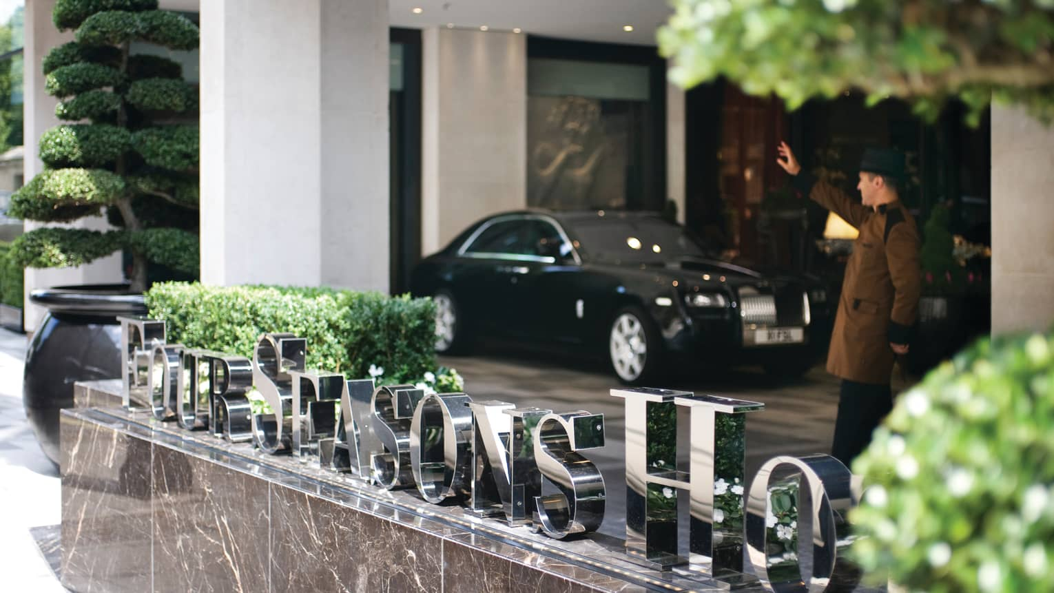 Steel Four Seasons Hotel sign on marble by doorman in uniform, black luxury car