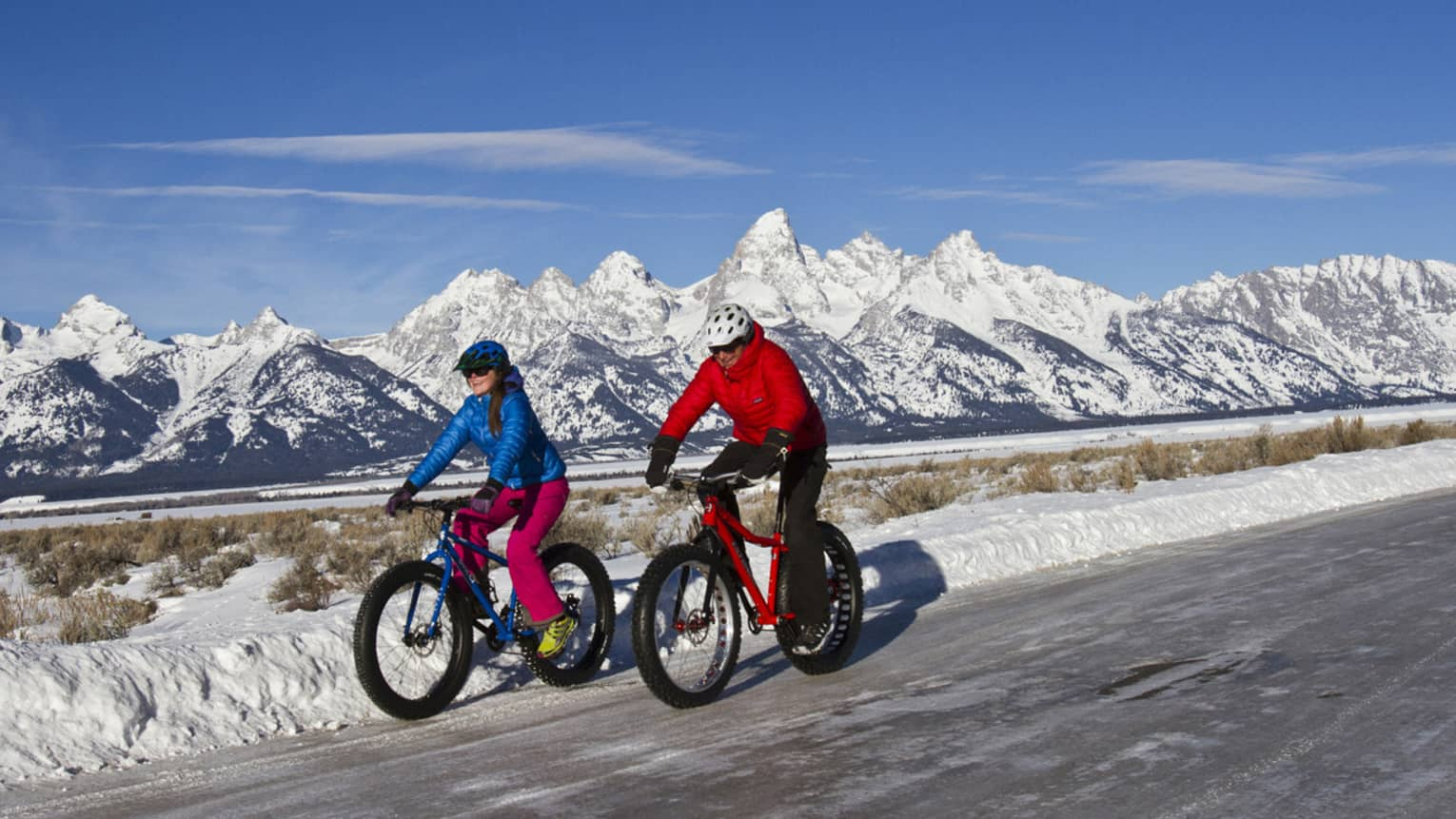 A man and woman bike down a path, snow-capped mountains and blue sky in the background