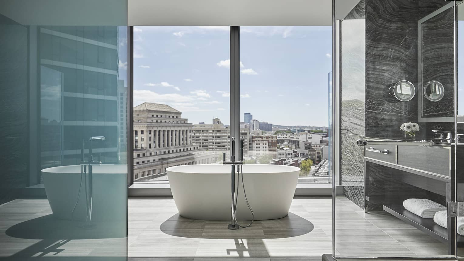 A free-standing tub sits in the middle of a large bathroom, overlooking downtown boston through floor to ceiling windows