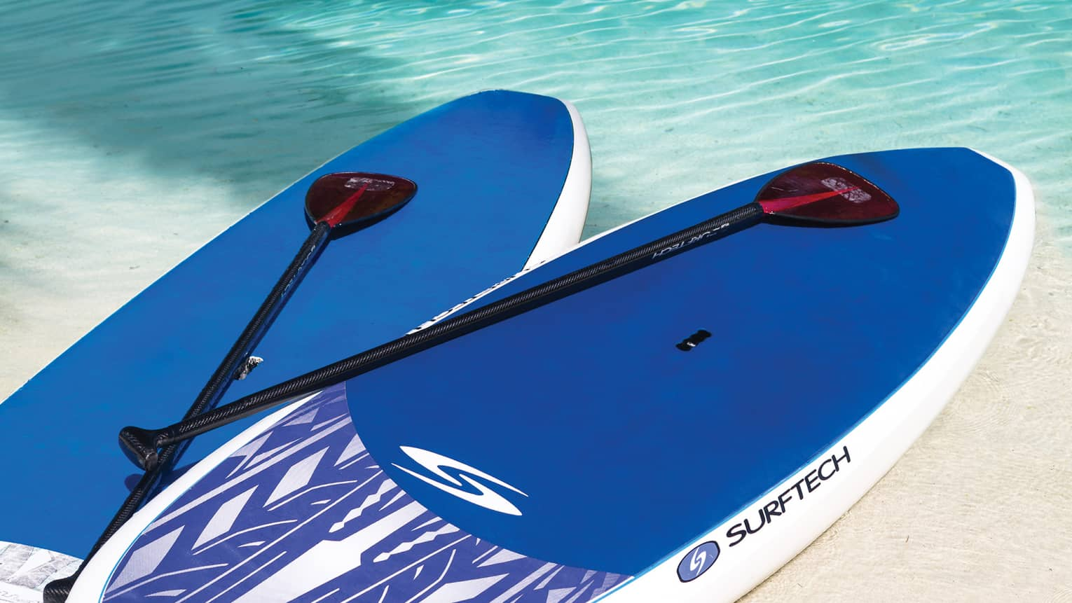 Close-up of two blue stand-up paddleboards and paddles