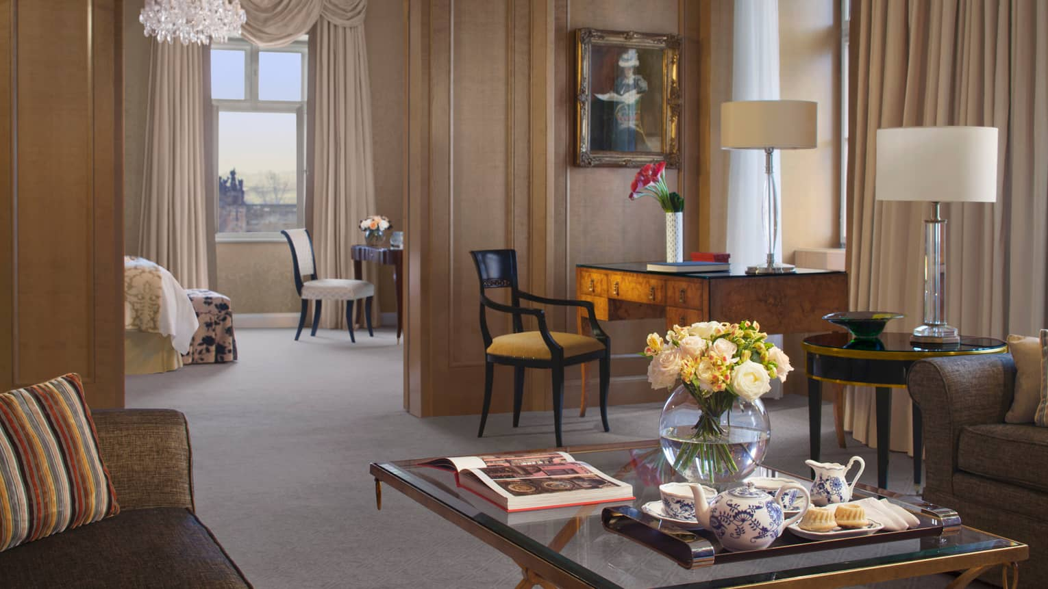 Premier Suite living room, glass coffee table with open book, round glass vase with white roses, tea service
