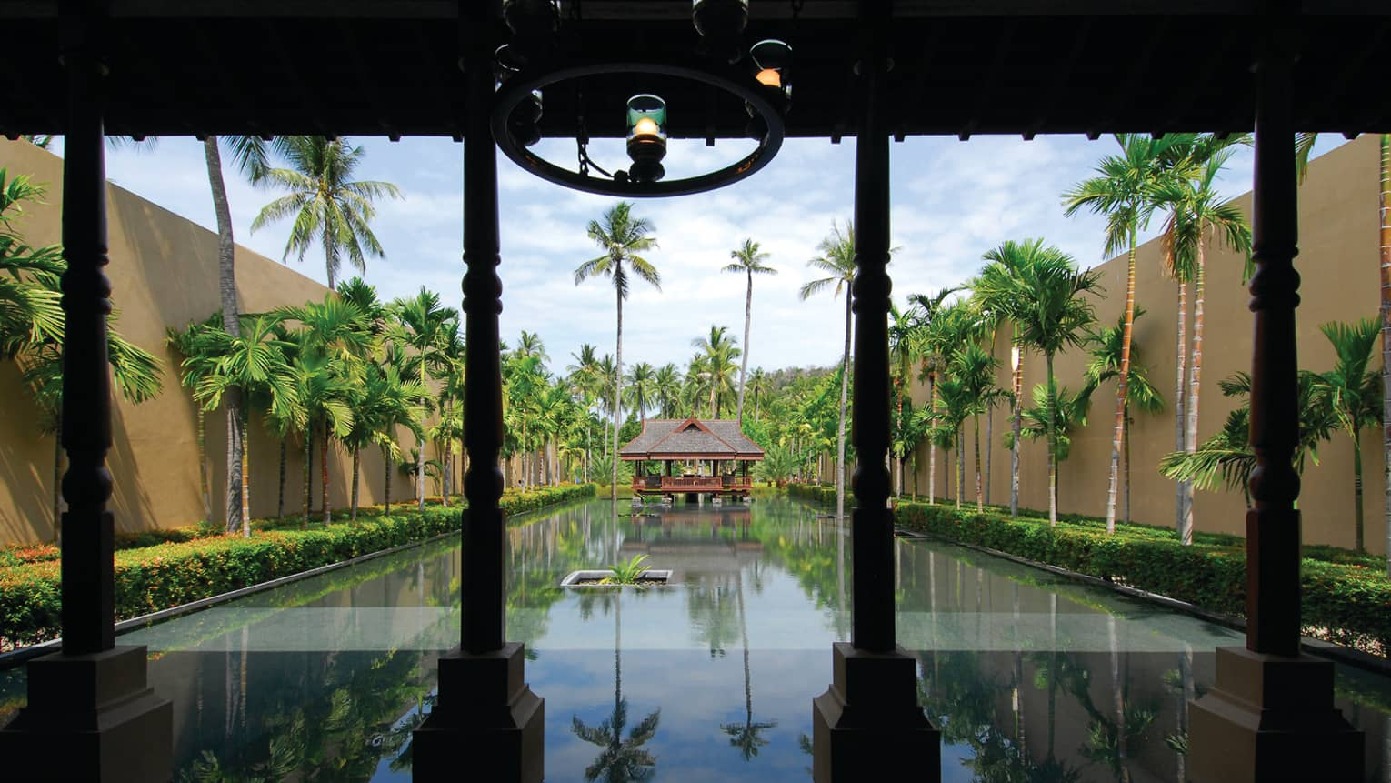 Wood gazebo at end of long reflection pond lined with palm trees