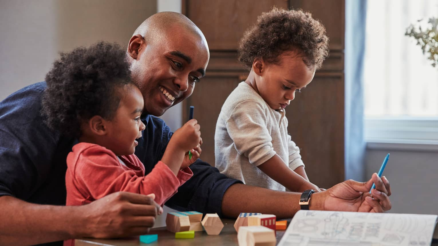 A smiling man and two toddler girls play with blocks