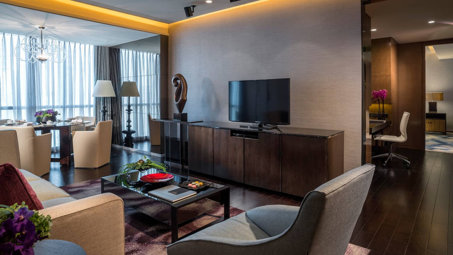 Ambassador Suite modern seating area, dresser and TV, sculpture, dining table near window