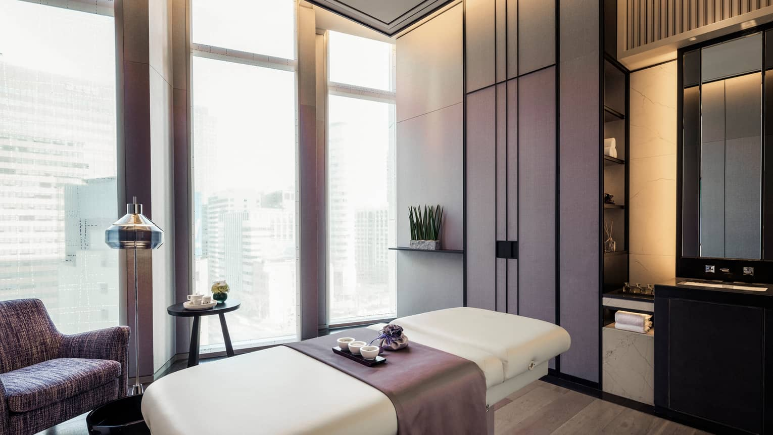 Purple accent chair, blanket over massage table with Spa tray by floor-to-ceiling windows, shades