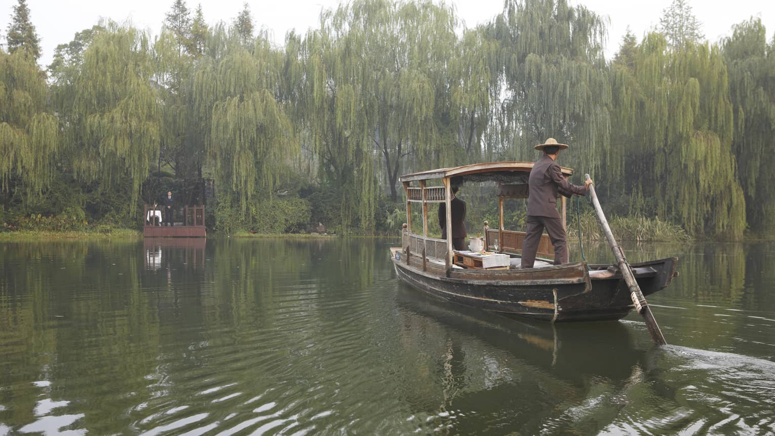 A guest arriving at a dock in Hangzhou, surrounded by weeping willows
