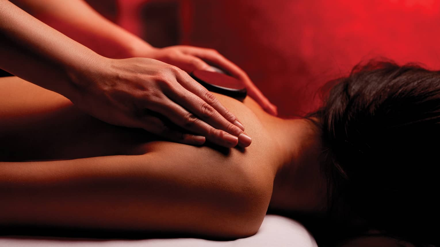Hands rub woman's bare shoulders during Fusion Massage in spa