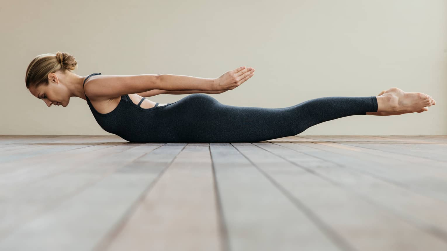 Woman wearing black spandex workout gear balances in plank position on floor