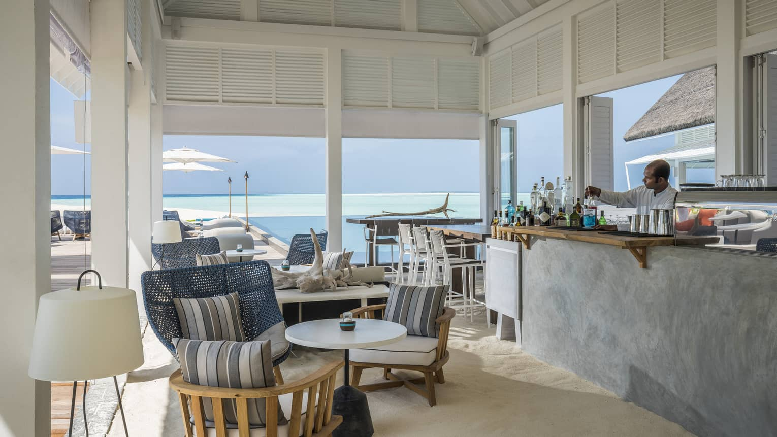 A comfortable, oceanside bar at the Blu Beach Club with plush chairs and a variety of cocktail selections