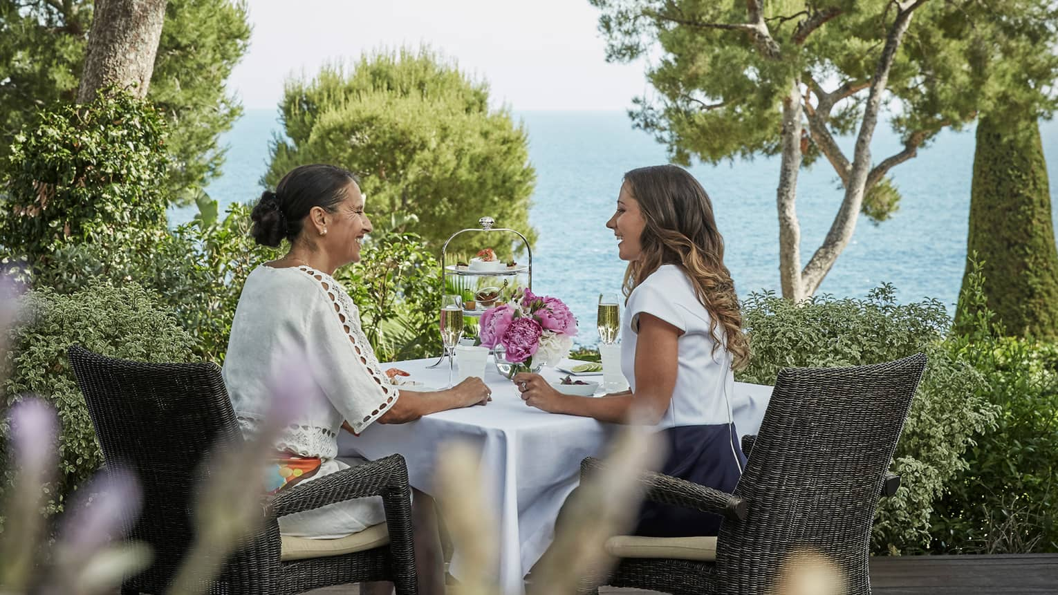 Two women sip Champagne at patio table with dessert tray, sea views