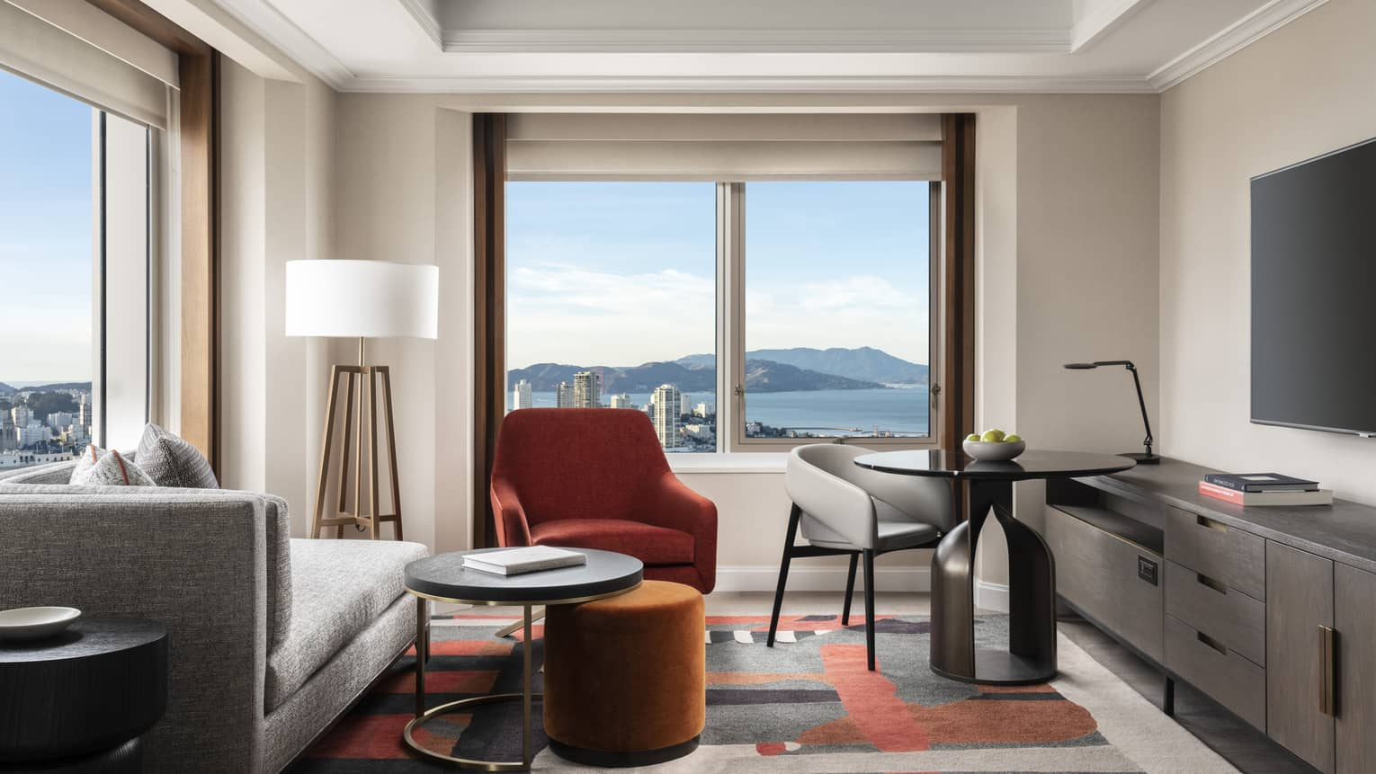 Living area in a hotel room, with corner views of San Francisco and bay