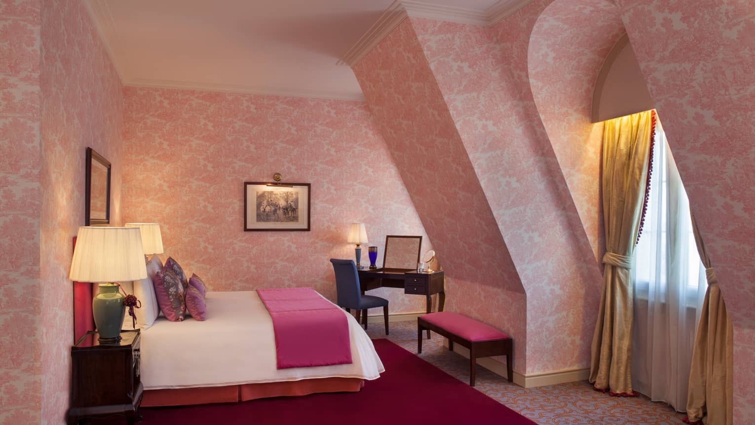 La Mansión Diplomatic Premier Suite with pink-patterned wallpaper on sloped walls, bed, bench and desk