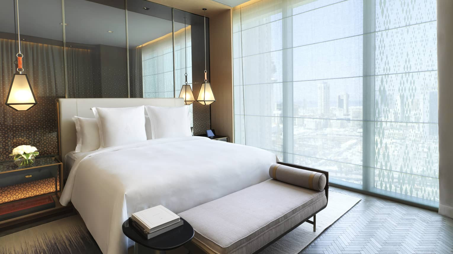 Four Seasons Executive Suite bed in front of mirror wall, hanging lights, beside floor-to-ceiling window
