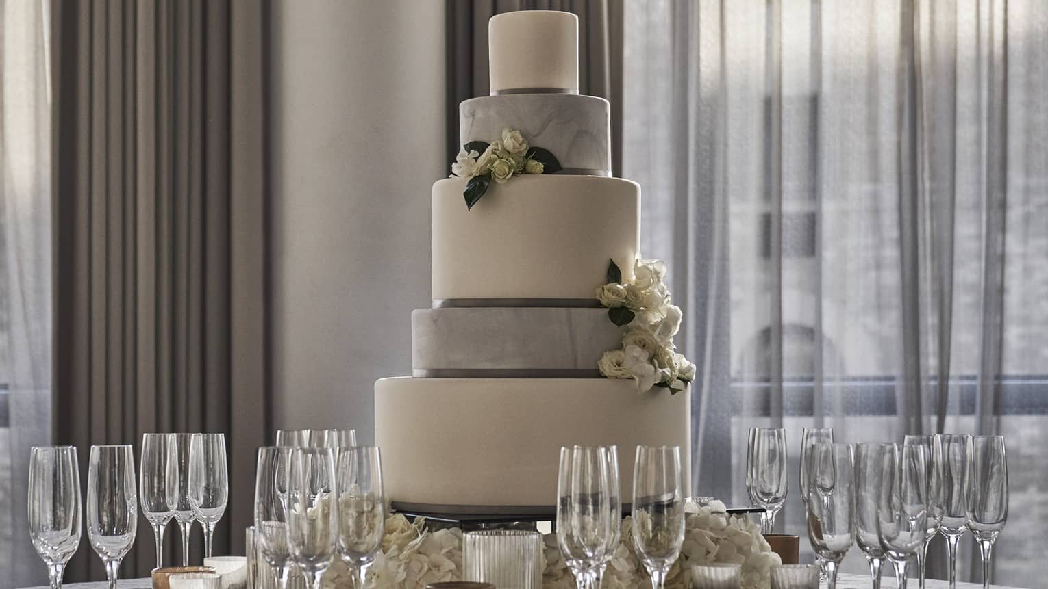 Tiered wedding cake on round banquet table with Champagne glasses