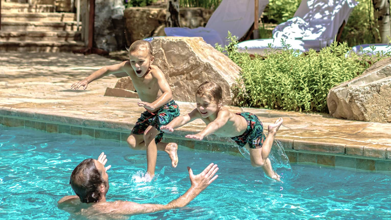 Two young boys jump into their father's outstretched arms in an outdoor pool