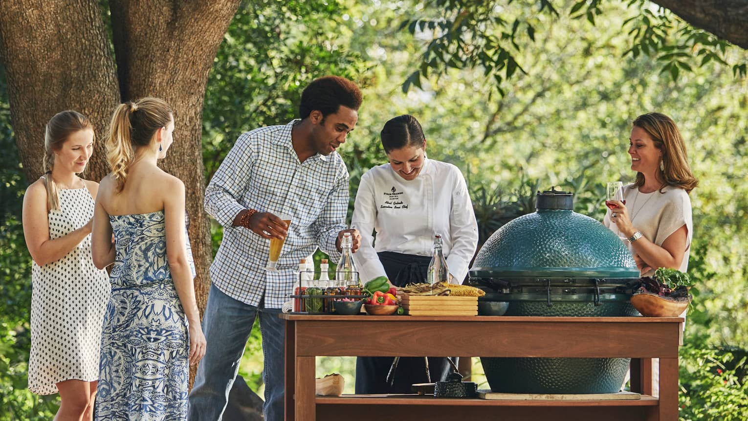Group of friends watch as chef prepares meal at outdoor garden barbecue