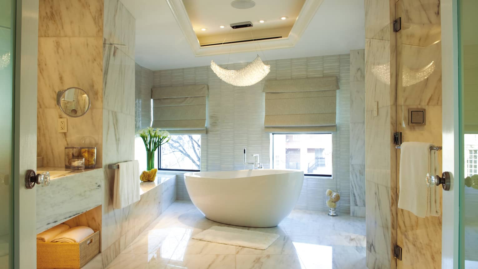 Royal Suite white marble bathroom with large, modern freestanding tub near double windows