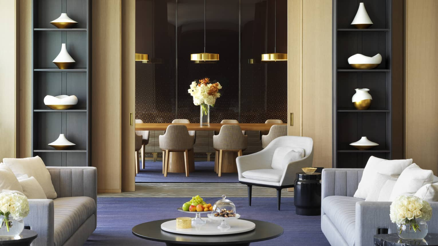 Modern dining table, gold lamps in private room behind lounge with tall bookshelves, sofas