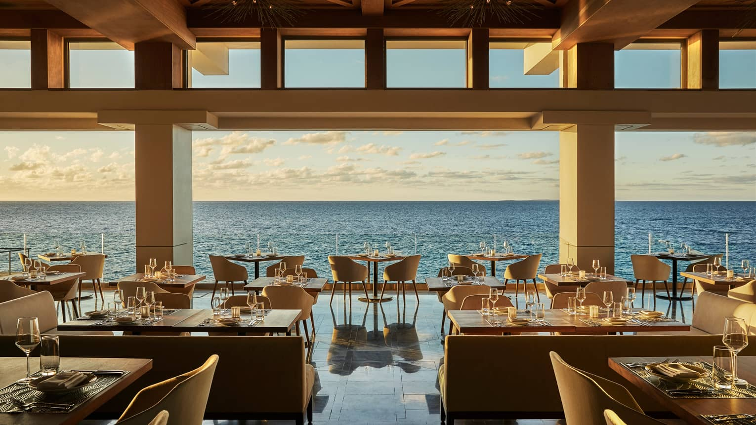 Elegant Coba open-air restaurant with dining tables and chairs, gleaming floors over open ocean