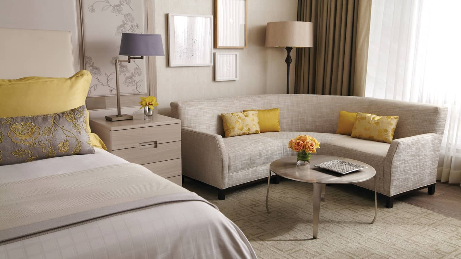 Yorkville Premier Room curved white sofa by bed, yellow accent pillows, yellow roses on table
