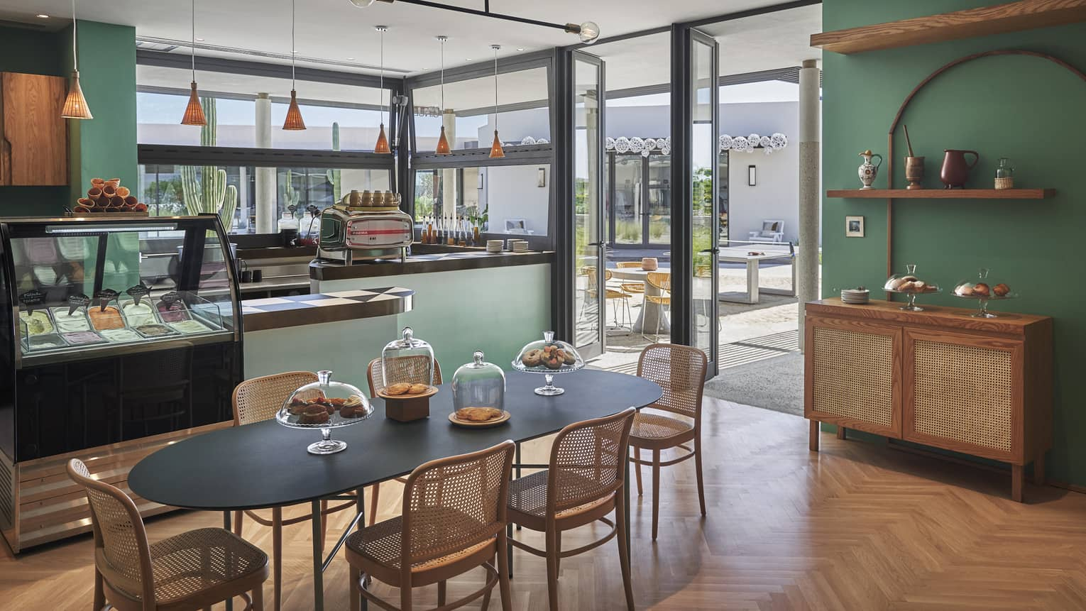 Green-walled Gingers dining area, black oval table and wicker chairs, food display case