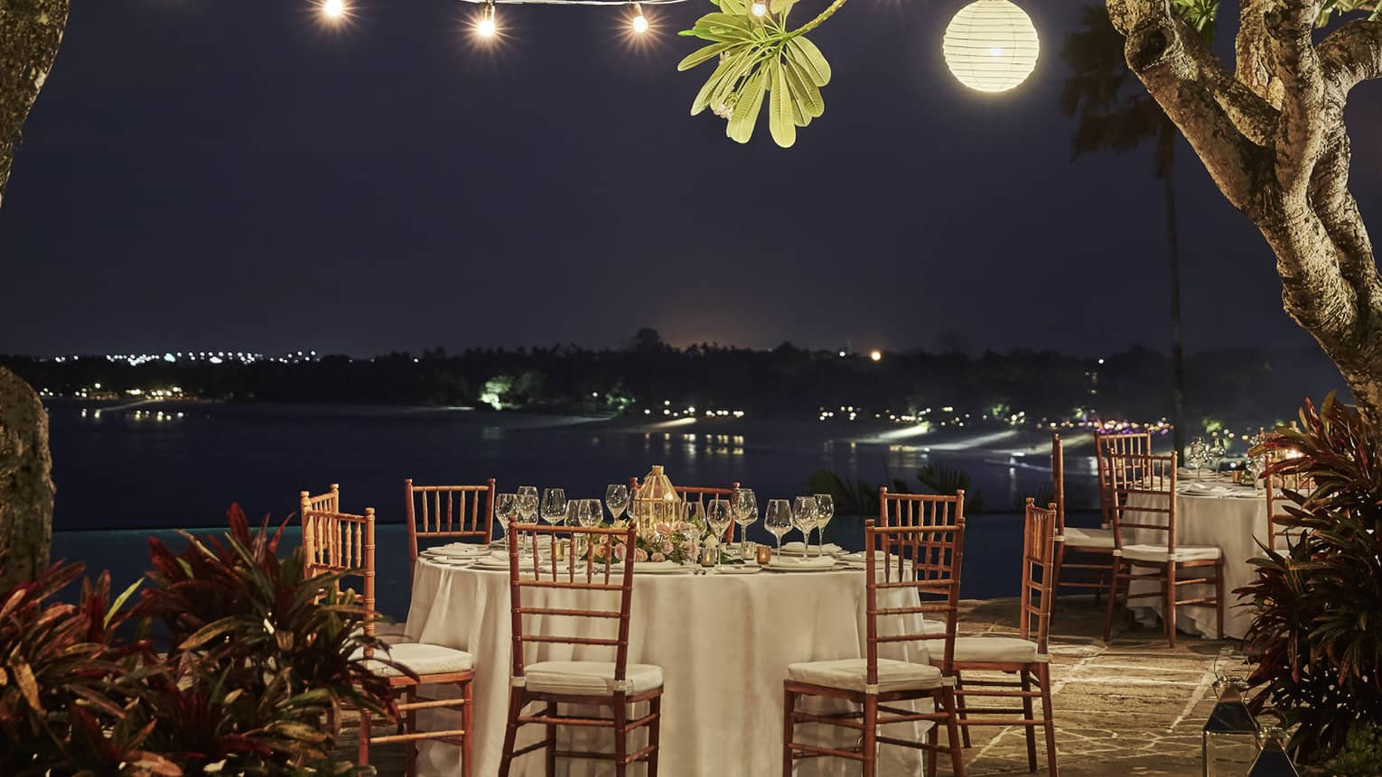 A romantic dinner table set outside under the night sky, with string lights and lanterns hanging in the trees above it