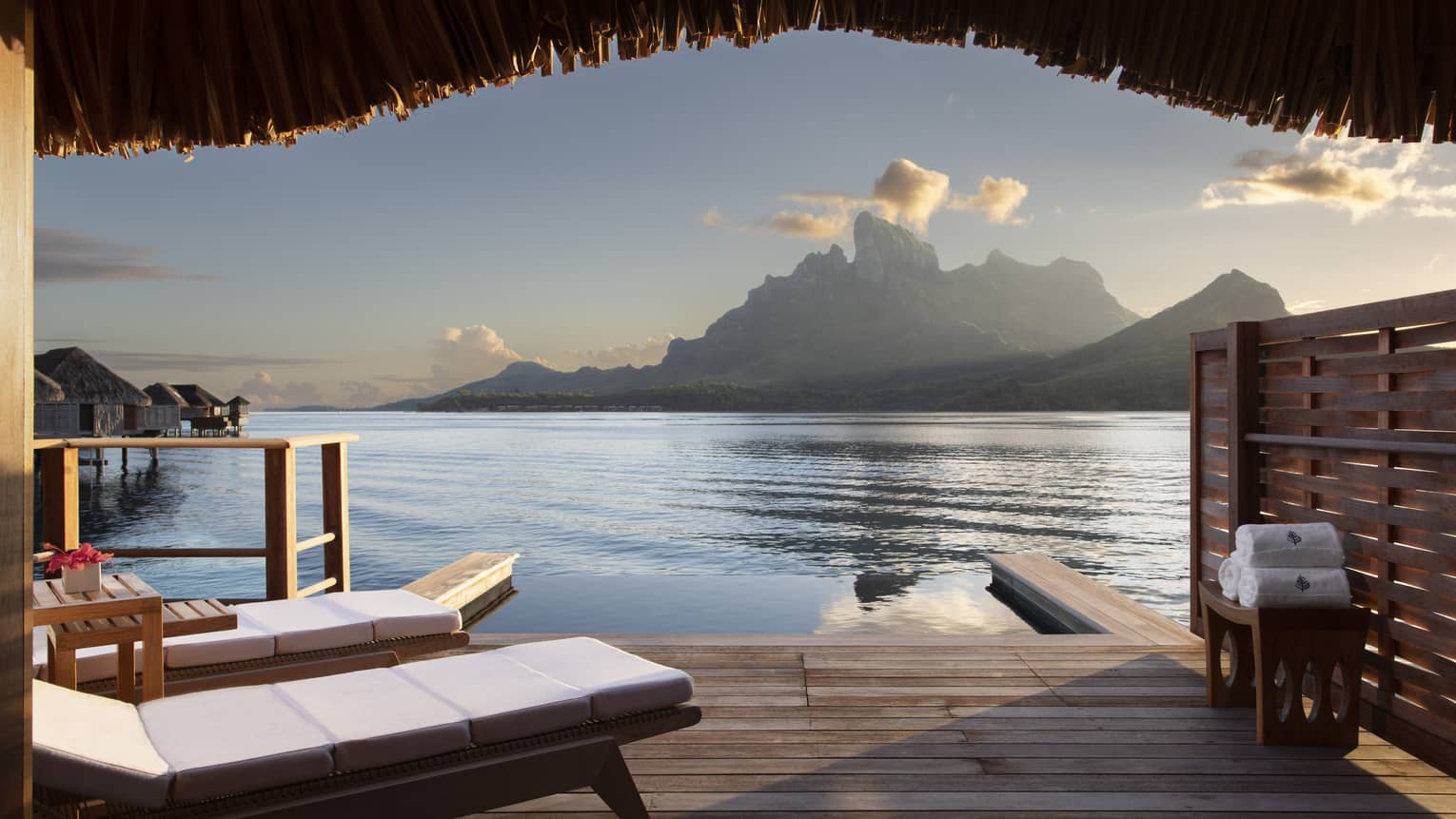 A view from a wooden Water Bungalow with white cushioned lounge chairs overlooking the ocean and mountains in the background at Four Seasons Bora Bora