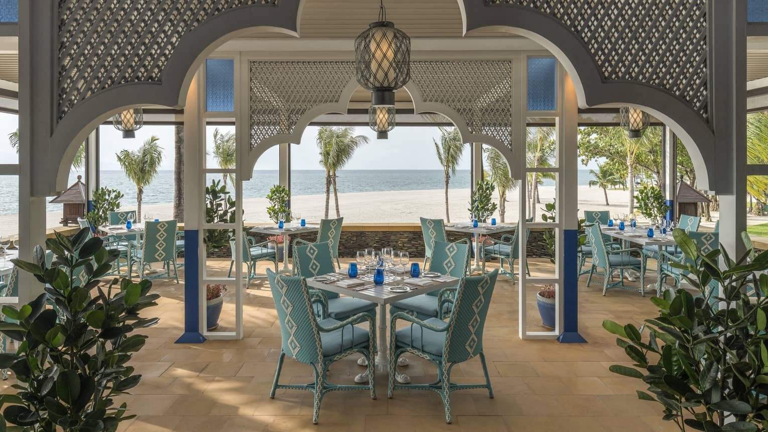 Upper Serai Restaurant dining area overlooking the beach with palm trees