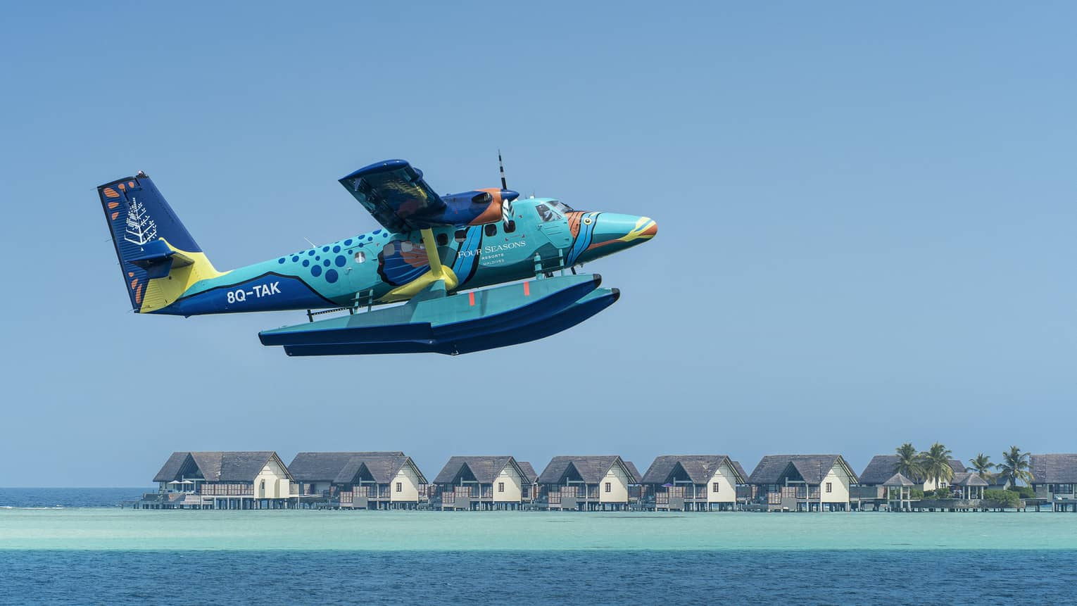 Maldives Sea Plane taking off with water villas and palm trees in the background