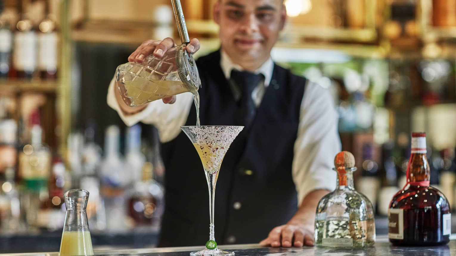 Bartender wearing black vest pours cocktail from crystal shaker into martini glass