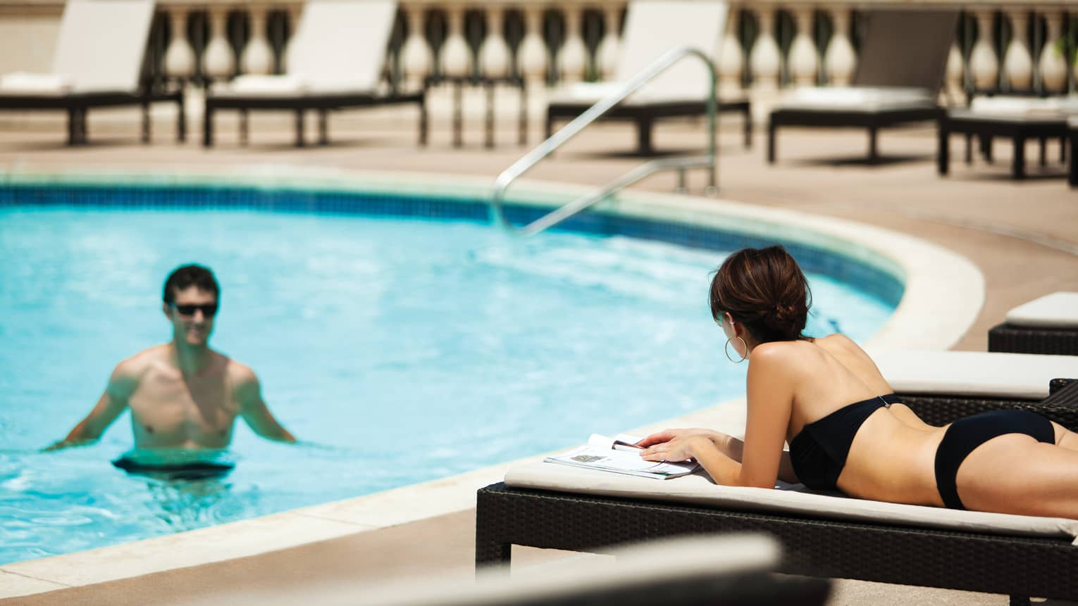 Man wades in outdoor swimming pool, looks up at woman in swimsuit lying on deck chair