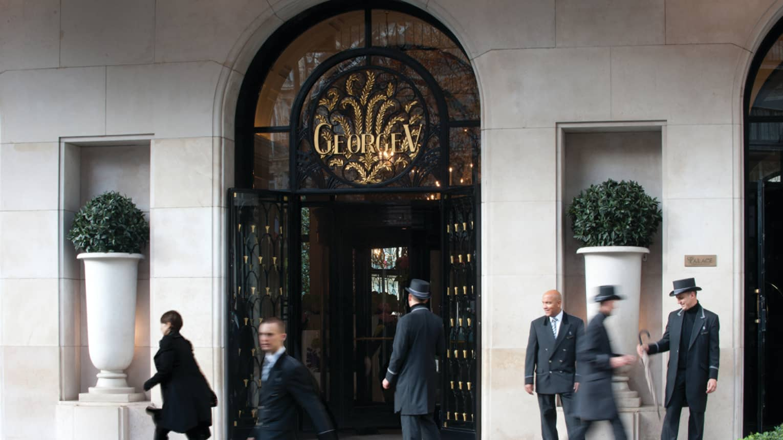 People walk quickly past doormen in hars at arched Four Seasons Hotel Paris front entrance