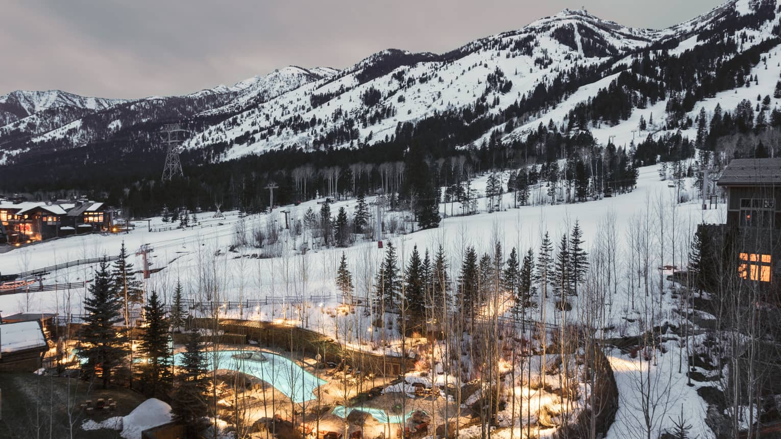 Aerial view of illuminated blue outdoor swimming pool through trees on snowy hill at dusk