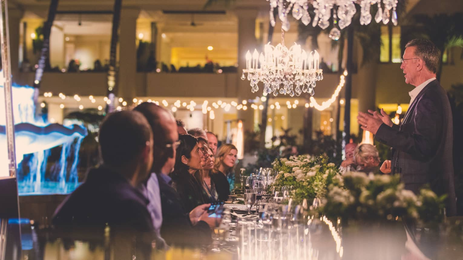 Guests seated at a bar underneath crystal chandeliers listen attentively to a wine sommelier