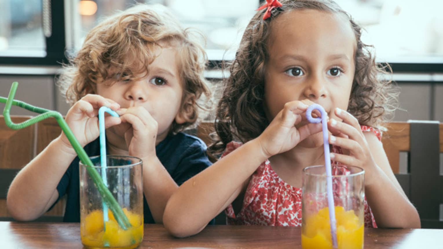 Two small children with curly hair sit side-by-side drinking juice with swirly straws at Club 760