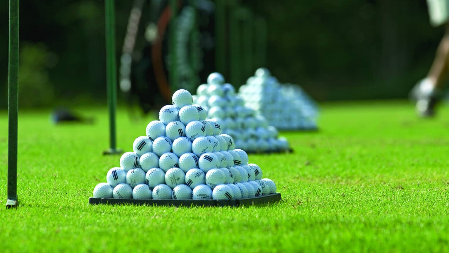 Golf balls arranged in pyramid formations in row on golf course green