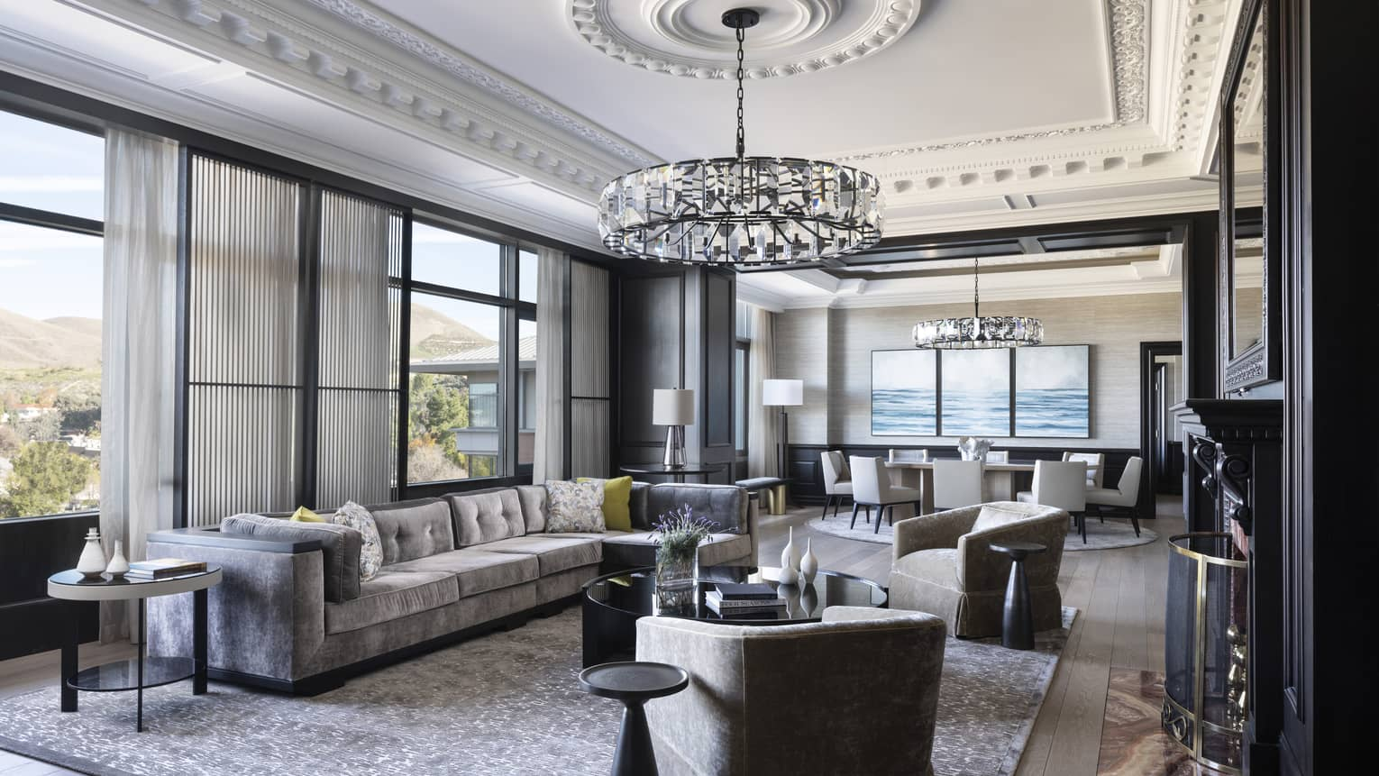Presidential Suite featuring a chic, grey, L-shaped sofa under a ceiling that boasts elaborate crown molding and a crystal chandelier