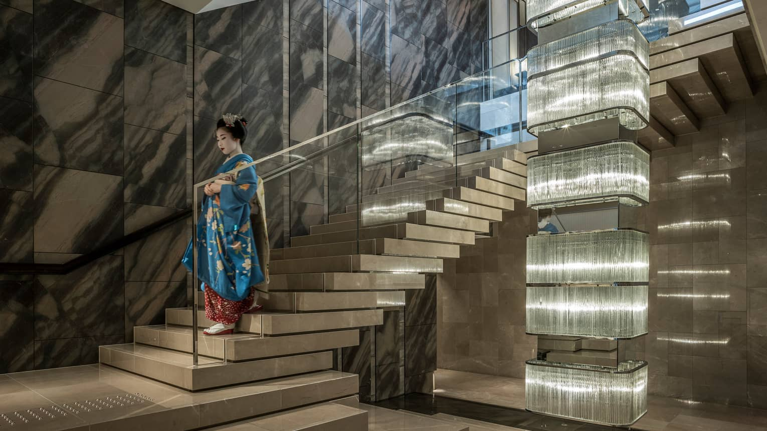 Geisha wearing traditional kimono, make-up descends down marble and glass staircase