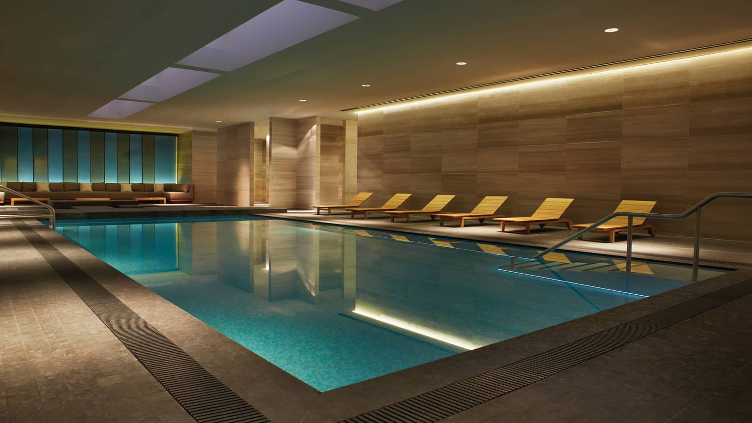 Illuminated indoor swimming pool with wood chairs on deck under granite walls
