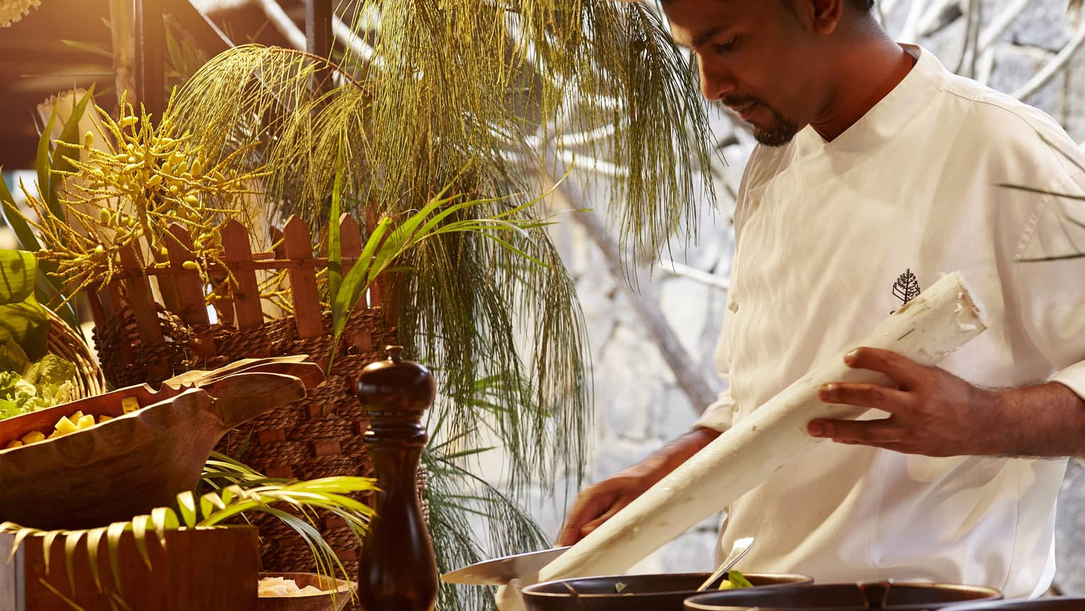 Zilwa Night, chef in white uniform carves long white stick by pepper mill