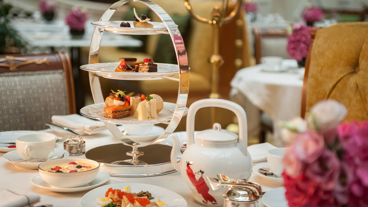 Elegant tea service on dining table, white pout, three-tiered tray with little cakes, sandwiches