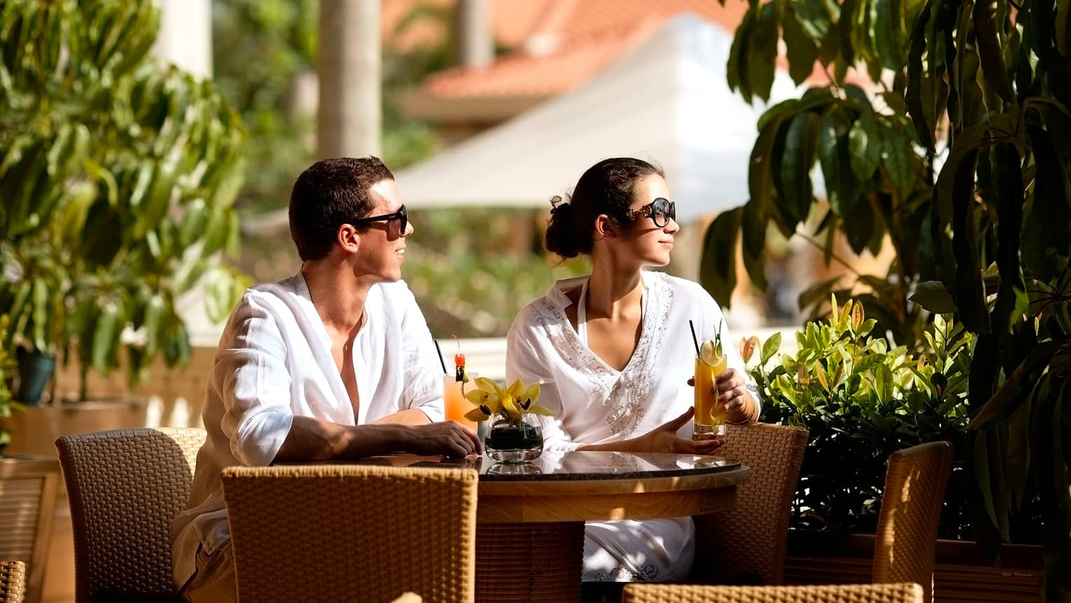 Couple wearing white linen shirts, sunglasses drinks cocktails at patio table