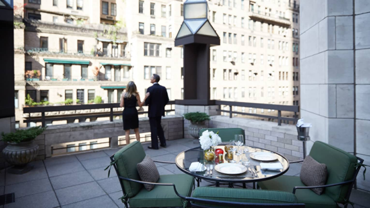 Man and woman in business suits look out from rooftop patio with table, plush chairs
