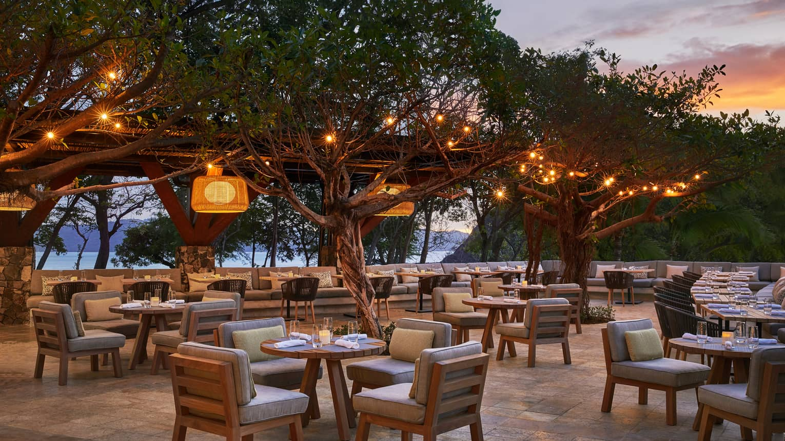 Patio tables, chairs with plush cushions on patio under trees with hanging lights, at sunset