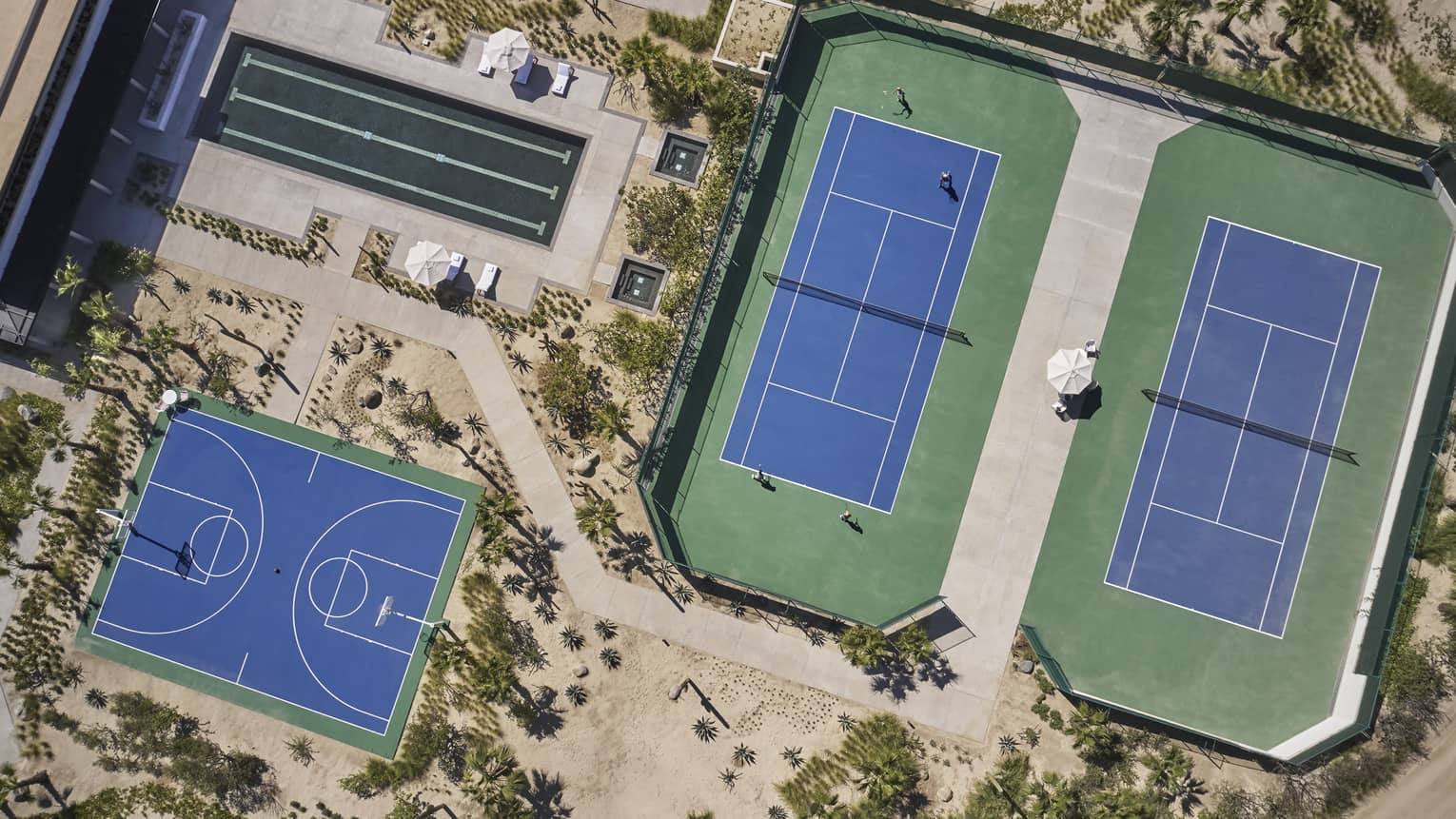 Aerial view of two green and blue tennis courts, one long rectangular pool and one blue basketball court surrounded by sand and greenery