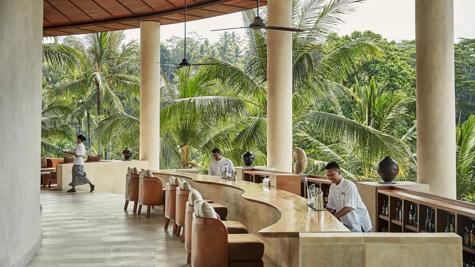 Smiling bartenders behind long wood-and-stone bar under white pillars of resort balcony, palm trees in background