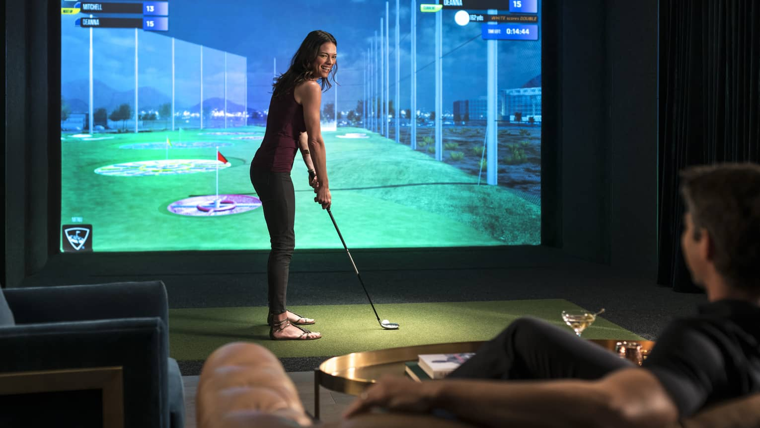 A couple playing a golf simulator and enjoying a drink.